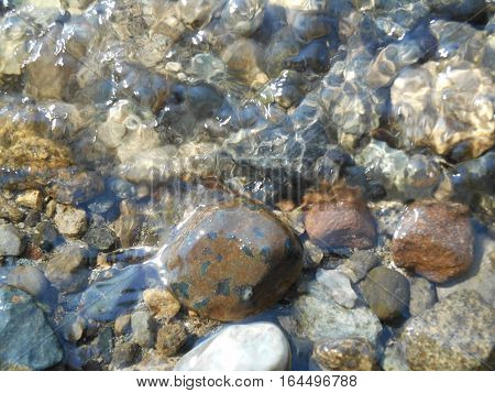 pebbles and stones under water random pattern glistening in sunlight.