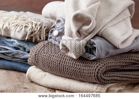 stack of of warm clothes stack of jeans on the old wooden background