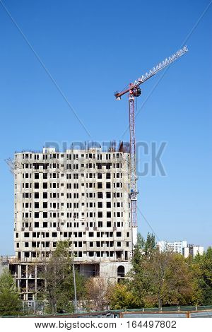 Big hoisting tower crane and top section of modern construction building in a city over cloudless sky