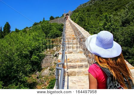 Young woman walking on the defensive wall of Ston town Peljesac Peninsula Croatia. Ston was a major fort of the Ragusan Republic