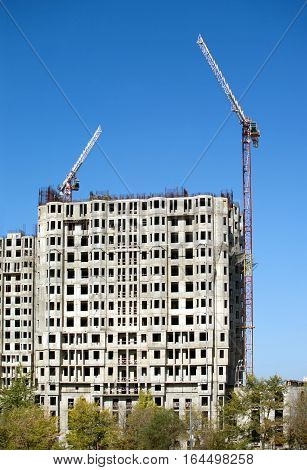 Big hoisting tower cranes and top section of modern construction buildings over cloudless sky