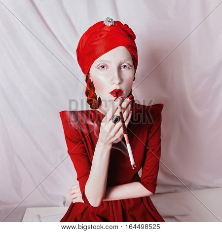 redhead smoking girl with red lips and a red turban on a white background woman with a white skin with a ring on her finger and a mouthpiece in hand a bright unusual appearance