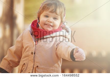 A smiling blond, happy girl thumbs up while playing in the park. Autumn and Winter fashion model. Empty copy space for editor's text.