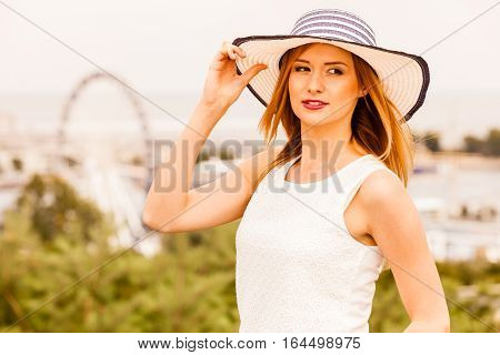 Female fashion trendy summer clothes concept. Attractive young woman wearing sun hat and white top fashionable summeral style outdoor shot on sunny day
