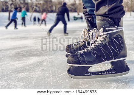Close-up of ice skating shoes on a rink with people skating in the background