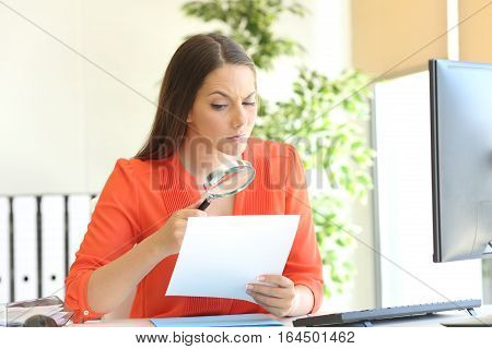 Businesswoman examining a contract meticulously with a magnifying glass at office