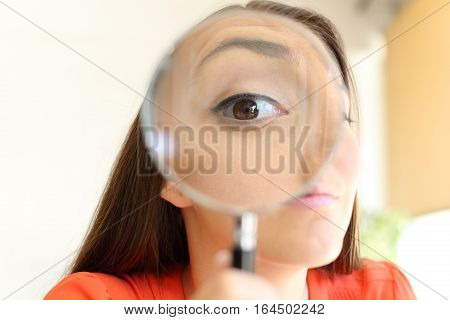 Front view close up of a suspicious businesswoman eye watching you with a magnifying glass