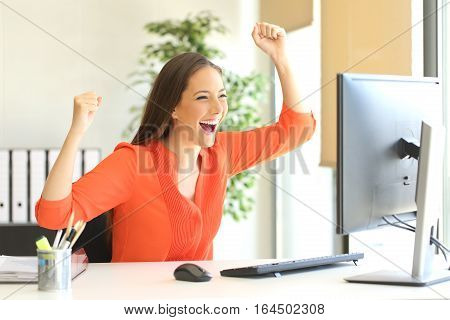 Excited entrepreneur wearing an orange blouse reading good news on line in a desktop computer monitor in the office