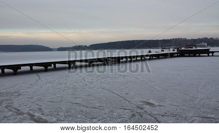 Frozen lake and a wooden jetty on a cloudy day