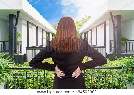 Woman lower back painful injury and looking through the window. Businesswoman backache and injury at - office syndrome concept