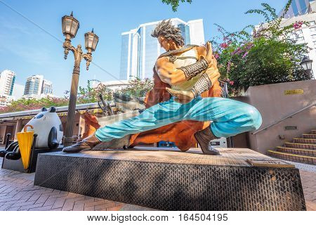 Hong Kong, China - December 5, 2016: Cloud and On On and Guy Guy, statues of famous characters, in Hong Kong Avenue of Comic Stars, Kowloon Park. Urban skyline background of Tsim Sha Tsui District.