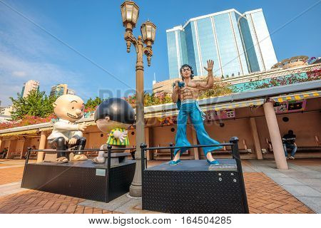 Hong Kong, China - December 5, 2016: Bruce Lee and Cowboy, statues of famous characters, in Hong Kong Avenue of Comic Stars, Kowloon Park. Urban skyline of Tsim Sha Tsui.