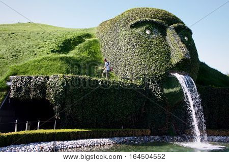 WATTENS AUSTRIA - 07 May 2009: Man worker cutting grass with lawn mower near the entrance of Swarovski Crystal Worlds entitled 'The Giant'.