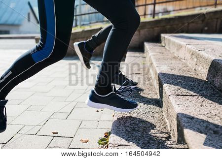 Legs of two young unrecognizable athletes running on stairs outside on sunny autumn day.Trail runners training for cross country race.