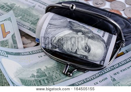 Black wallet with one hundred dollars inside. Background of hundred dollars banknotes and different coins denominations.