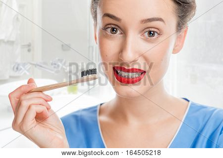 Portrait of confused woman with tooth braces holding a toothbrush at the bathroom. Woman worried about tooth cleaning with braces