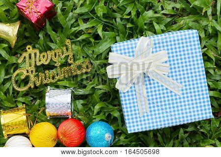 Blue Gift box on green lawn and gold text of Merry ChristmasFestival gift concept and Christmas or New Year's Day.
