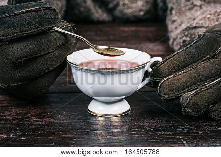 Human hands in suede gloves holding white cup of cambric tea and teaspoon. Front view