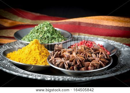 Assortment of dried spices including star of anise pink peppercorns curry and parsley.