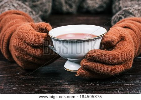 Human hands in rusty gloves holding white cup of cambric tea. Front view