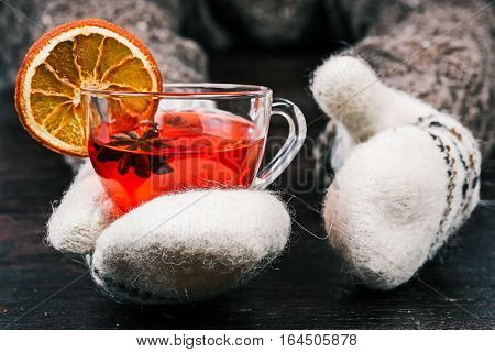 Human hands in white mittens holding cup of spicy fruit tea. Front view