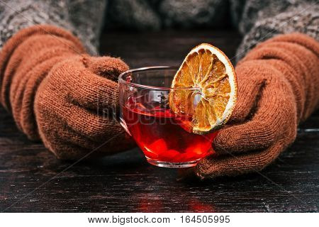 Human hands in rusty gloves holding cup of spicy fruit tea. Front view