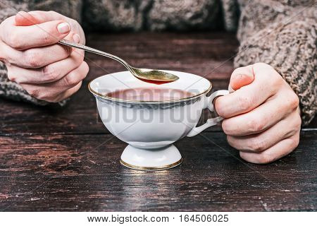 Human hands holding white cup of cambric tea. Front view