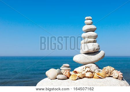 pyramid of white stones and shells on a background of blue sky and sea