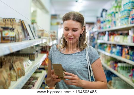 Woman choosing rice in a grocery store.