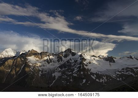 Breathtaking view from the top of the nearby snow-covered mountain range, lit by the evening sun, against the sky with bright clouds