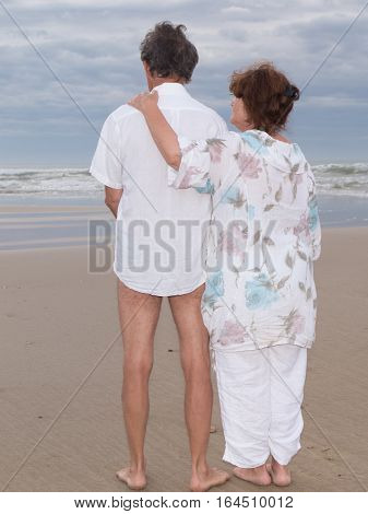 A Couple Of Retirees Standing On The Beach Contemplating The Ocean