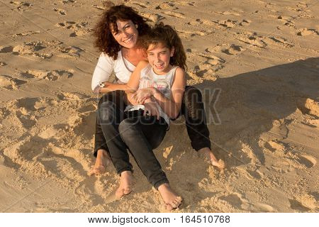 A Mother Tickles Her Daughter On The Beach During The Summer Holidays