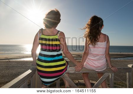 A Mother And Her Back Girl Look At The Sun That Will Soon Set