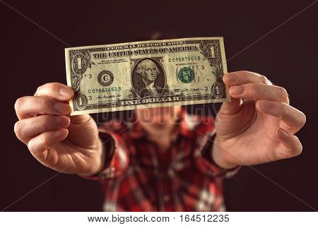 Woman offering one dollar bill selective focus