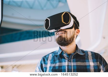 Young man trying vr goggles. Boy is watching some interesting video on screen. Close up