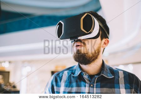 Young man trying vr goggles. Attractive guy watching something astonished on its screen. Close up