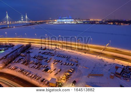 Saint-Petersburg Russia - January 2 2017: Top view of a cityscape at night cable-stayed bridge the frozen river a football stadium and parking lot.
