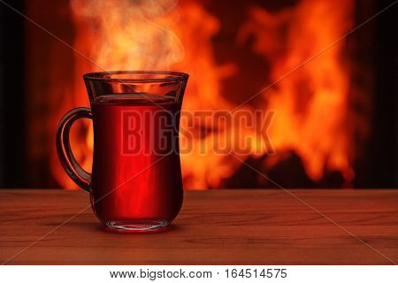 A tea glass at the table in front of a fireplace