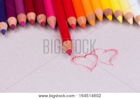 Multicolored pencils on beige pastel paper coarse grain grunge texture. Waveform border from colour pencils. Copy space. Place for text. Valentines day decoration.