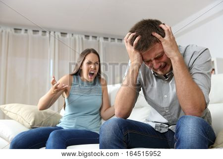 Couple arguing. Wife shouting to her desperate husband sitting on a couch in the living room at home