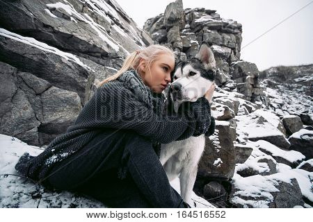 Girl with dog Malamute among rocks in winter. They sit on rocks among scattering of stones and snow. Girl hugs a dog's neck.