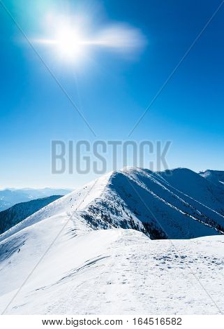 Snowy mountains with sun, beautiful european mountains, symbol of winter mountains, alpine mountain peak, mountains in winter