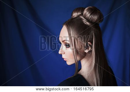 blonde woman with big blue eyes like a elf long white hair in a bun a girl with hairstyle and makeup in a green dress on a blue background portrait profile