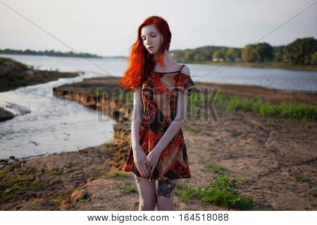 beautiful red-haired girl in sundress standing on the background of the river sunny summer day a woman with an unusual appearance with pale skin european