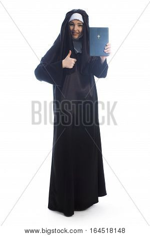 Young nun advertises bible and shows thumbs. Full length photo on white background.