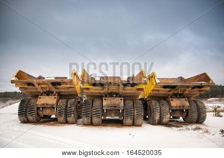 Three yellow empty trucks in the quarry.