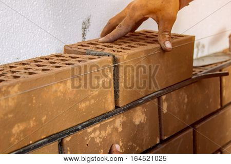 Bricklayer lays bricks under unravel. construction work