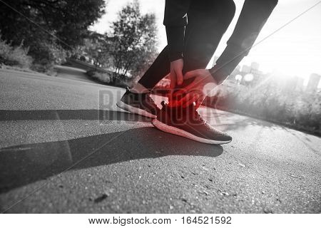 Broken twisted ankle - running sport injury. Athletic man runner touching foot in pain due to sprained ankle