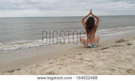 young pretty woman or cute girl with sexy flexible body practicing yoga or gymnastics in swimsuit on sandy beach with sea water and cloudy sky on natural background cpy space