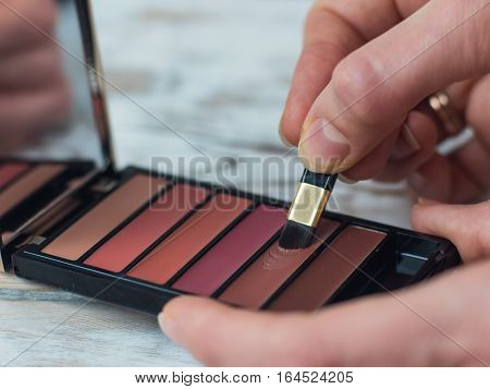 Make-up artist holding a palette of colorful eyeshadows and a brush, close up